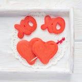 De rode fluweelpannekoeken met xo ondertekenen, omhelzingen en kussen, en hart op houten dienblad, hoogste mening, vierkant Stock Fotografie