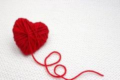 De rode garenbal zoals een hart op het wit haakt achtergrond Het romantische concept van de Valentijnskaartendag Rood die hart va royalty-vrije stock foto