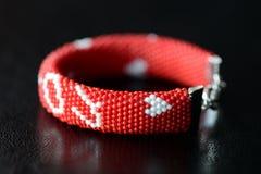 De rode geparelde armband van de valentijnskaartendag op een donkere achtergrond Royalty-vrije Stock Fotografie