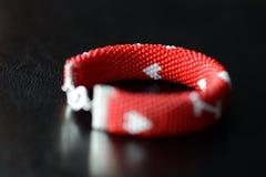 De rode geparelde armband van de valentijnskaartendag op een donkere achtergrond Royalty-vrije Stock Afbeeldingen