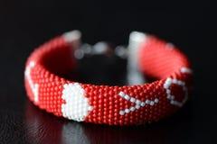 De rode geparelde armband van de valentijnskaartendag op een donkere achtergrond Stock Foto's