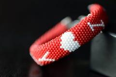 De rode geparelde armband van de valentijnskaartendag op een donkere achtergrond Stock Afbeelding