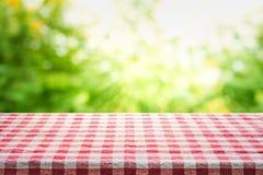 De rode geruite hoogste mening van de tafelkleedtextuur met abstracte groene bokeh stock afbeelding