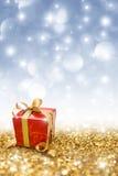 De rode gift op gouden schittert stock afbeeldingen