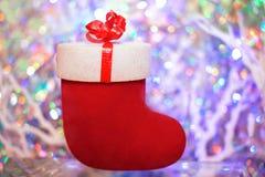 De rode gift voelde laars op een gekleurde achtergrond met bokeh Stock Foto's