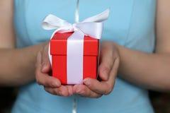 De rode giftdoos in vrouwelijke handen sluit omhoog, Valentine-gift stock fotografie