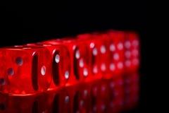 De rode gok dobbelt met bezinning over zwarte achtergrond, selectieve nadruk stock foto