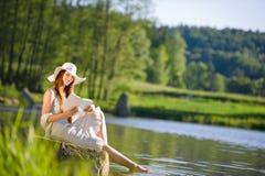 De rode haar romantische vrouw ontspant door meer met boek Stock Afbeeldingen