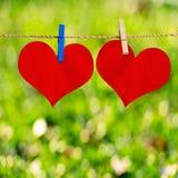 De rode hartvorm op notadocument maakt aan kabel vast Stock Afbeelding