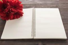 De rode het gerberabloemen en notitieboekje zijn op de houten achtergrond Stock Foto's