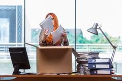 De rode hoofdvrouw die zich aan nieuw bureau bewegen die haar bezittingen inpakken stock foto