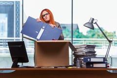 De rode hoofdvrouw die zich aan nieuw bureau bewegen die haar bezittingen inpakken stock foto's