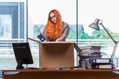 De rode hoofdvrouw die zich aan nieuw bureau bewegen die haar bezittingen inpakken royalty-vrije stock fotografie