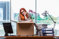 De rode hoofdvrouw die zich aan nieuw bureau bewegen die haar bezittingen inpakken stock fotografie