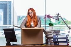 De rode hoofdvrouw die zich aan nieuw bureau bewegen die haar bezittingen inpakken royalty-vrije stock foto's