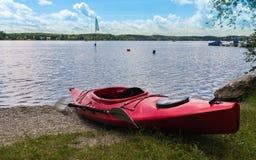 De rode kajak van de waterreis is klaar voor gebruik die op het strand van Wörthsee liggen Op de Achtergrond het meer met vlag,  stock fotografie
