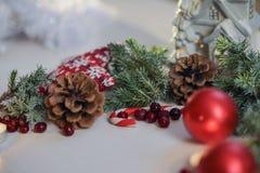 De rode Kerstmisballen met jeneverbes op witte achtergrond dienen en een brandende kaars in, gelukwens en magisch Stock Afbeeldingen