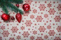 De rode Kerstmisornamenten en de Kerstmisboom op canvasachtergrond met rood schitteren sneeuwvlokken De kaart van Kerstmis Gelukk Royalty-vrije Stock Foto's