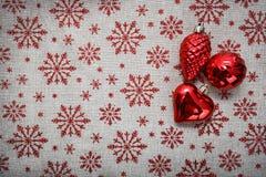De rode Kerstmisornamenten en de Kerstmisboom op canvasachtergrond met rood schitteren sneeuwvlokken De kaart van Kerstmis Gelukk Stock Foto