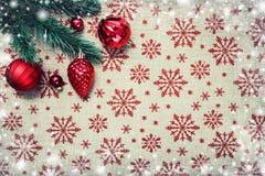 De rode Kerstmisornamenten en de Kerstmisboom op canvasachtergrond met rood schitteren sneeuwvlokken De kaart van Kerstmis Gelukk Stock Fotografie