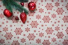 De rode Kerstmisornamenten en de Kerstmisboom op canvasachtergrond met rood schitteren sneeuwvlokken De kaart van Kerstmis Gelukk Royalty-vrije Stock Afbeeldingen