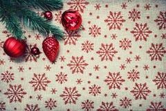 De rode Kerstmisornamenten en de Kerstmisboom op canvasachtergrond met rood schitteren sneeuwvlokken De kaart van Kerstmis Gelukk Stock Foto's