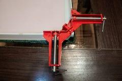 De rode klem houdt een hoek van doos stock afbeelding