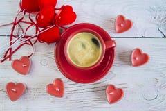 De rode kop van koffie, rode kaarsen vormt hart, rode hartdecoratie Stock Afbeelding