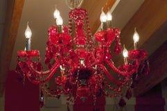 De rode kroonluchter van het kristalplafond met geparelde takken Stock Foto