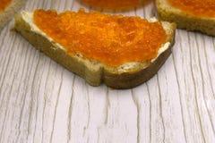De rode kuiten van de kaviaarzalm op een boterham en een boter stock afbeeldingen