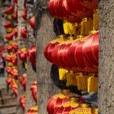 De rode lantaarns hangen tussen de bomen bij een park in Peking China stock afbeeldingen