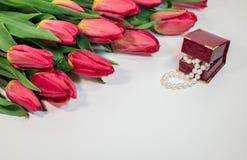 De rode lentetulpen met kleine doos met parels romantisch heden Royalty-vrije Stock Afbeeldingen
