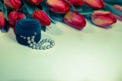 De rode lentetulpen met kleine doos met parels romantisch heden Stock Afbeelding
