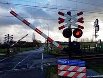 De rode lichten en de klokken waarschuwen ervoor dat de barrière op een spoorweg kruising daalt Royalty-vrije Stock Foto's