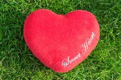 De rode liefde van het stoffenhart op groen gras stock foto