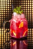 De rode limonade van de fruitcocktail in uitstekende kruik stock foto