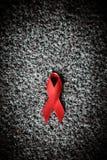 De rode lintvoorlichting op vrouwen menselijke hand verouderde witte achtergrond: Stock Afbeelding