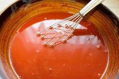 De rode marinade met peper en tomatenpuree in een kom met zwaait Stock Afbeeldingen