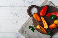 De rode oranjegele zoete groene paprika's op lijst sluiten omhoog Stock Foto's