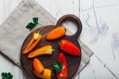 De rode oranjegele zoete groene paprika's op lijst sluiten omhoog Royalty-vrije Stock Afbeeldingen
