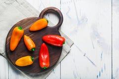 De rode oranjegele zoete groene paprika's op lijst sluiten omhoog Stock Fotografie