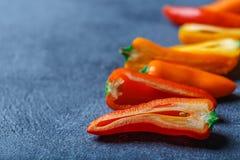 De rode oranjegele zoete groene paprika's op lijst sluiten omhoog Stock Afbeeldingen