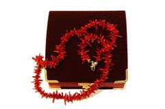 De rode parels van het koraal (halsband) en karmozijnrode fluweeldoos. Stock Foto's