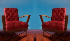 De rode paren bewapenen stoelen op houten en blauwe achtergrond stock fotografie
