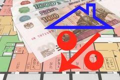 De rode percenten ondertekenen op een achtergrond van geld en tekening van een woningbouw stock afbeeldingen