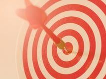 De rode pijl die van het bullseyepijltje doelcentrum van dartboard raken Concept succes, doel, doel, voltooiing stock fotografie