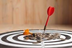 De rode pijltjepijl raakte het centrumdoel van dartboard en geldmuntstuk Stock Afbeeldingen