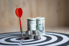 De rode pijltjepijl raakte het centrumdoel van dartboard en geldmuntstuk Stock Foto