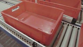 De rode plastic dozen worden bewogen langs een roltransportband stock video