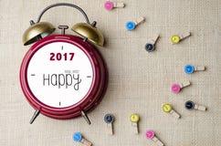 De rode retro klok van de alarmklok met Gelukkig Nieuwjaar 2017 en kleren Stock Afbeeldingen